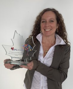 A picture of a woman with curly hair holding a leaf-shaped glass trophy