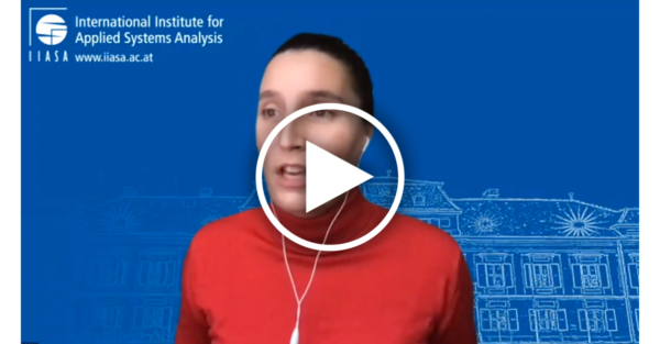 a white woman in a red shirt over a blue background with a play button overlaid