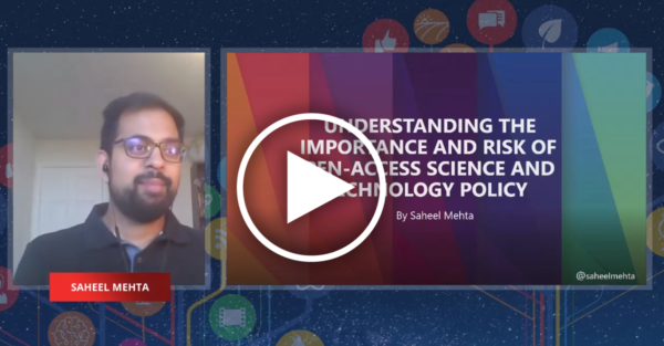 an indian man next to a presentation with a rainbow background, bearing the title of his talk