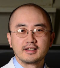 headshot of an asian man with glasses and a labcoat