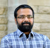 Headshot of an indian man with a beard and glasses