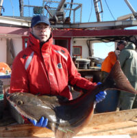 Photo of a white man holding a fish on a fishing vessel