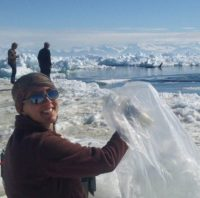 a woman holding a plastic bag on a glacier, with two people in the background