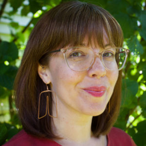 photo of a white woman with glasses and geometric earrings in front of a tree