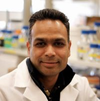 headshot of an indian man in a white coat, with a lab in the background