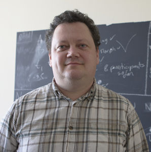 photo of a white man in front of a chalkboard
